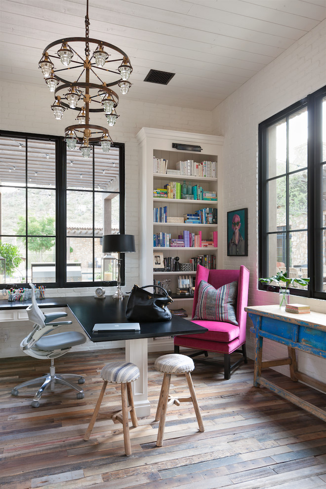 Inspiration for a mid-sized farmhouse built-in desk medium tone wood floor study room remodel in Phoenix with white walls and no fireplace