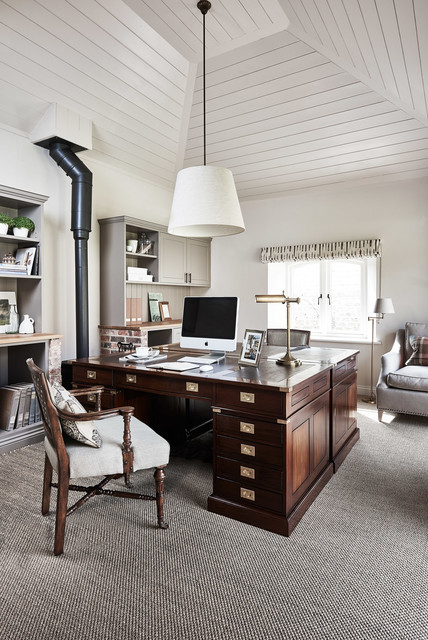 Country freestanding desk carpeted study room photo in Gloucestershire with white walls and a wood stove