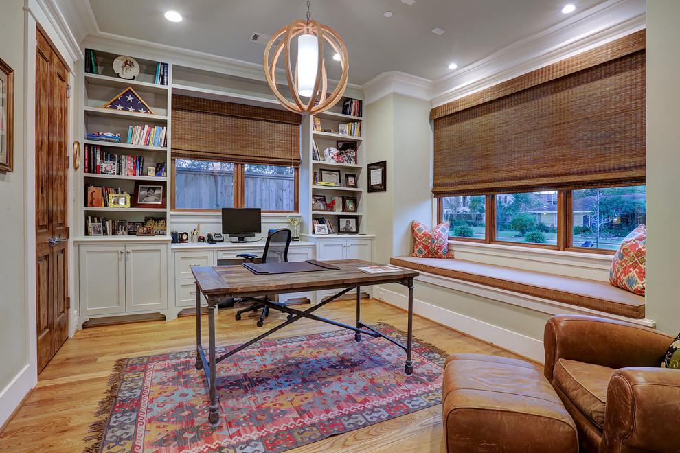 Elegant freestanding desk medium tone wood floor and beige floor study room photo in Houston with beige walls