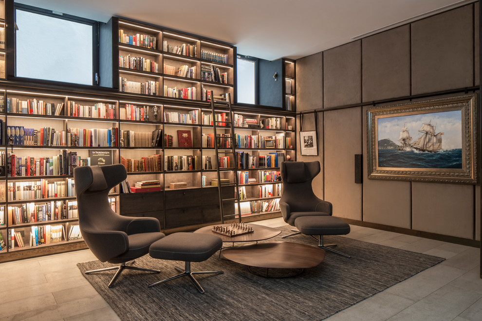 Example of a mid-sized minimalist gray floor home office library design in London with gray walls
