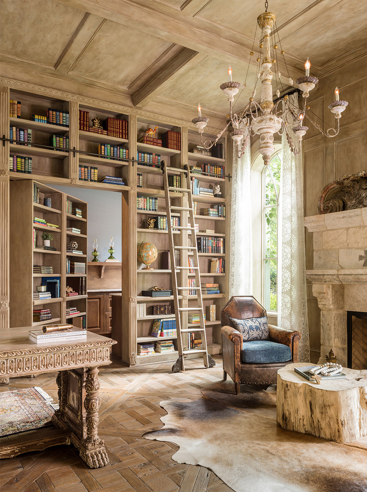 Inspiration for a mediterranean freestanding desk medium tone wood floor home office library remodel in New York with beige walls, a standard fireplace and a stone fireplace