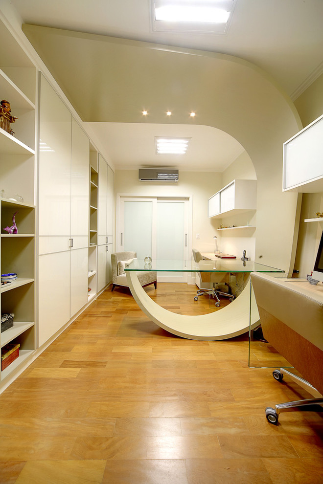 Inspiration for a contemporary medium tone wood floor home office remodel with beige walls