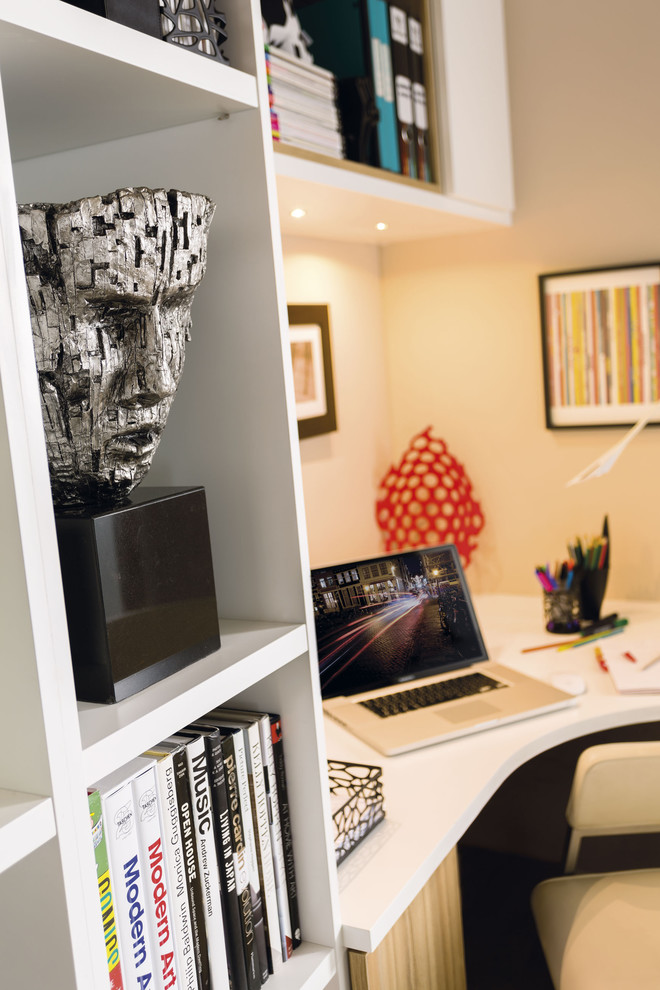 Study room - small contemporary built-in desk medium tone wood floor and brown floor study room idea in Manchester with white walls