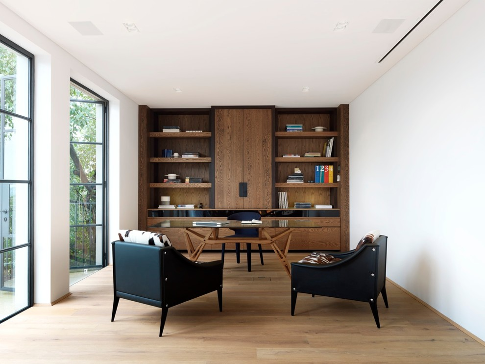 Study room - large contemporary freestanding desk medium tone wood floor study room idea in Sydney with white walls