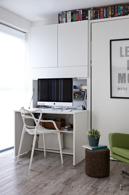 Photo of a contemporary study in London with white walls, a built-in desk and light hardwood flooring.