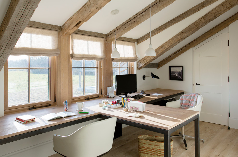 Example of a large farmhouse built-in desk light wood floor and brown floor study room design in Boston with white walls