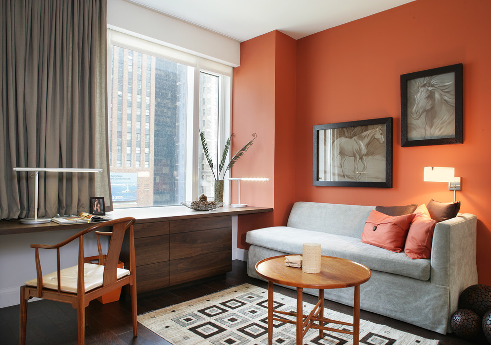 Inspiration for a contemporary built-in desk home office remodel in New York with orange walls