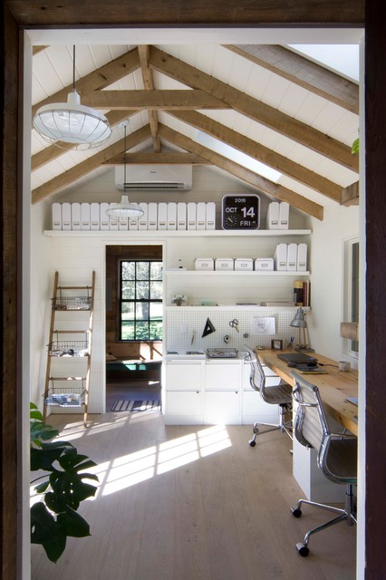 Home office - country built-in desk light wood floor home office idea in New York with white walls