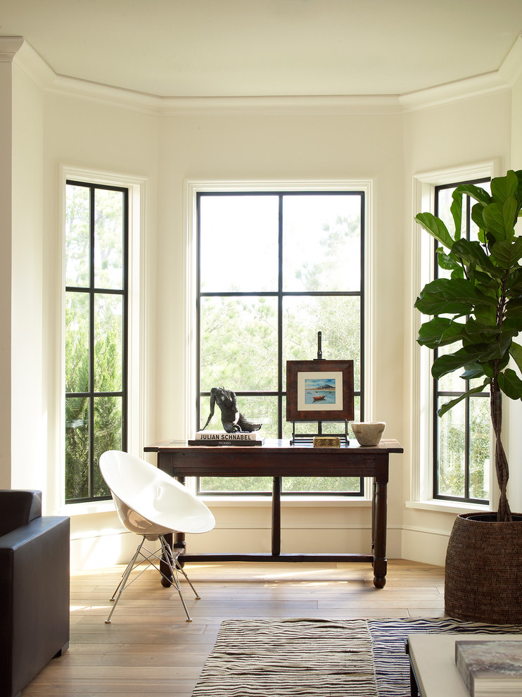 Example of a transitional freestanding desk light wood floor and beige floor home office design in Houston with beige walls