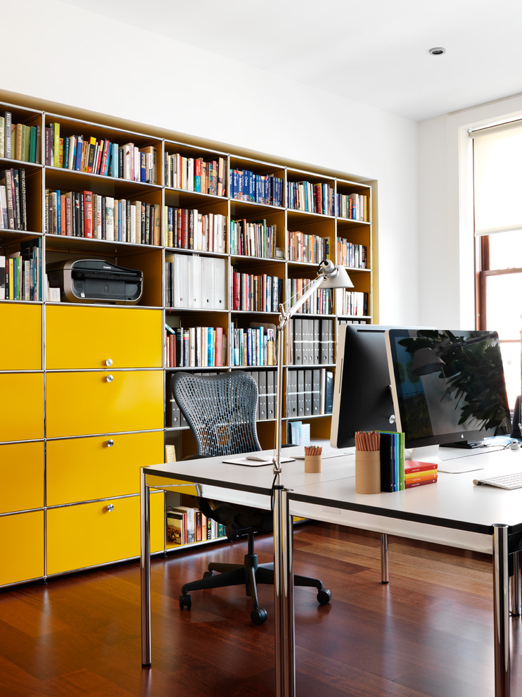 Example of a large trendy freestanding desk medium tone wood floor study room design in New York with white walls