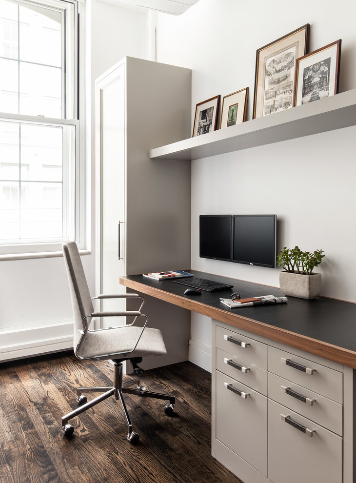 Inspiration for a contemporary built-in desk dark wood floor study room remodel in New York with white walls