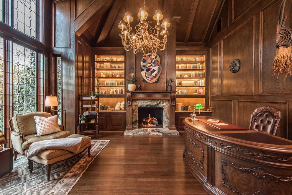 ロサンゼルスの広いトラディショナルスタイルのおしゃれなホームオフィス・書斎 (ライブラリー、茶色い壁、濃色無垢フローリング、標準型暖炉、石材の暖炉まわり、自立型机) の写真