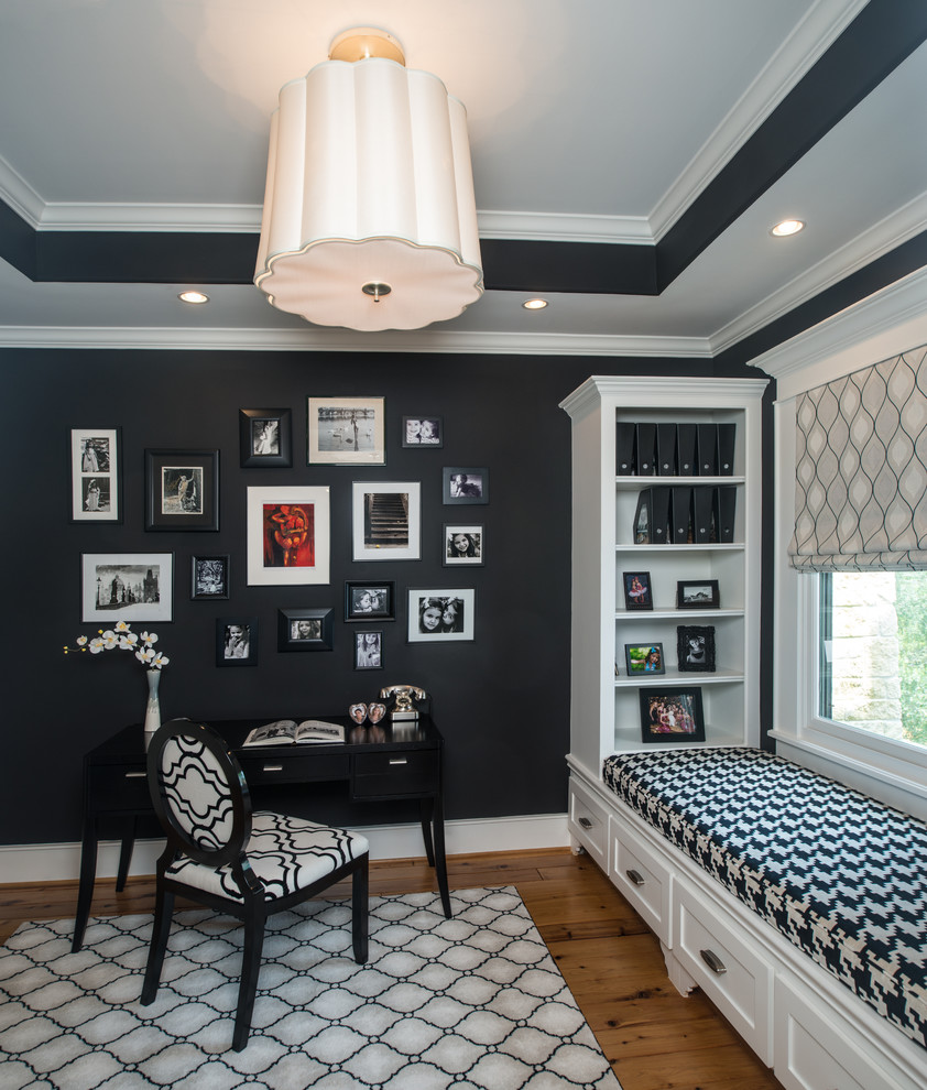 Study room - mid-sized traditional freestanding desk light wood floor study room idea in Houston with black walls and no fireplace