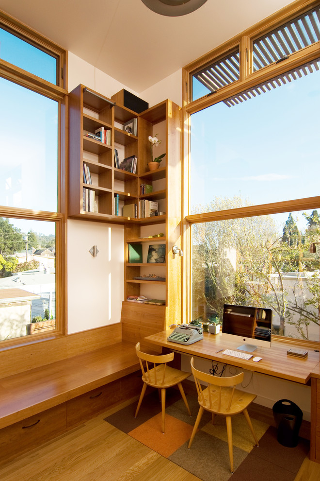 Example of a mid-sized trendy built-in desk medium tone wood floor home office design in San Francisco with white walls and no fireplace