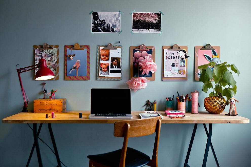 Inspiration för ett litet eklektiskt hemmabibliotek, med blå väggar och ett fristående skrivbord