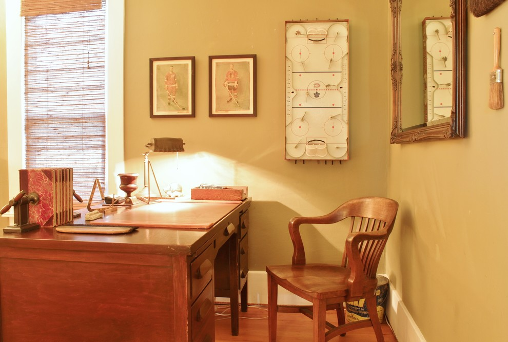 Mid-sized cottage freestanding desk medium tone wood floor home office photo in Seattle with beige walls