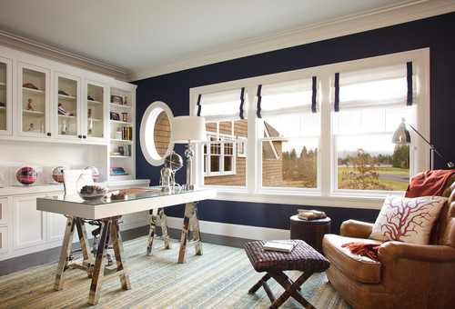 A home office with a beach inspired theme featuring white built-in cabinets, a whimsical desk, navy blue/indigo blue walls and white wood work.