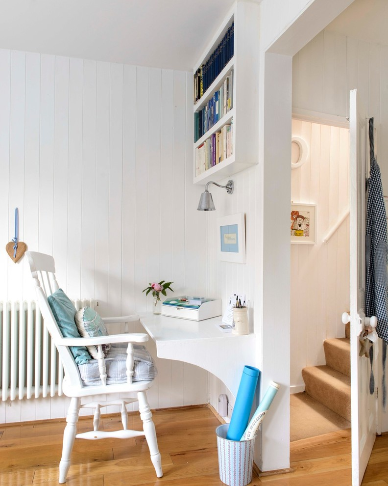 Home office - small coastal built-in desk medium tone wood floor home office idea in Kent with white walls