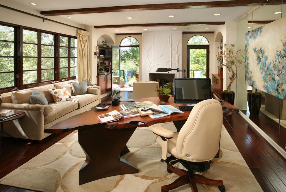 Example of a large transitional freestanding desk dark wood floor and brown floor study room design in Los Angeles with beige walls, a standard fireplace and a plaster fireplace