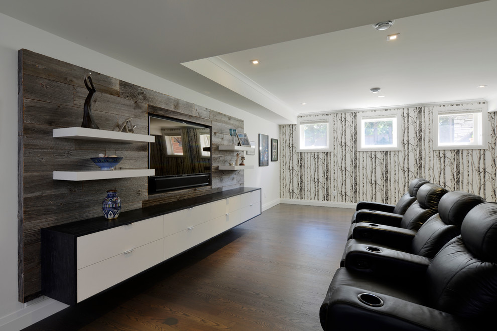 Inspiration for a large contemporary enclosed dark wood floor home theater remodel in Toronto with white walls and a media wall
