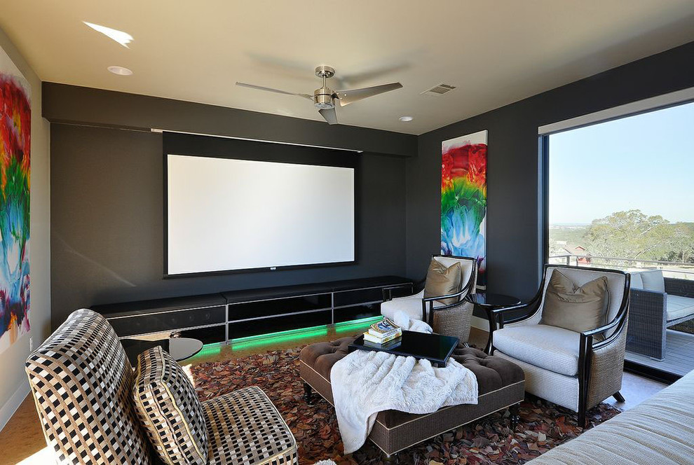 Example of a trendy enclosed home theater design in Austin with black walls and a projector screen