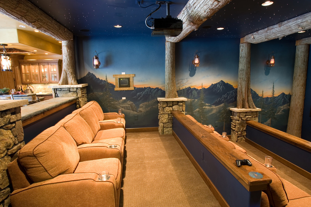 Example of a mountain style enclosed home theater design in Denver with a projector screen