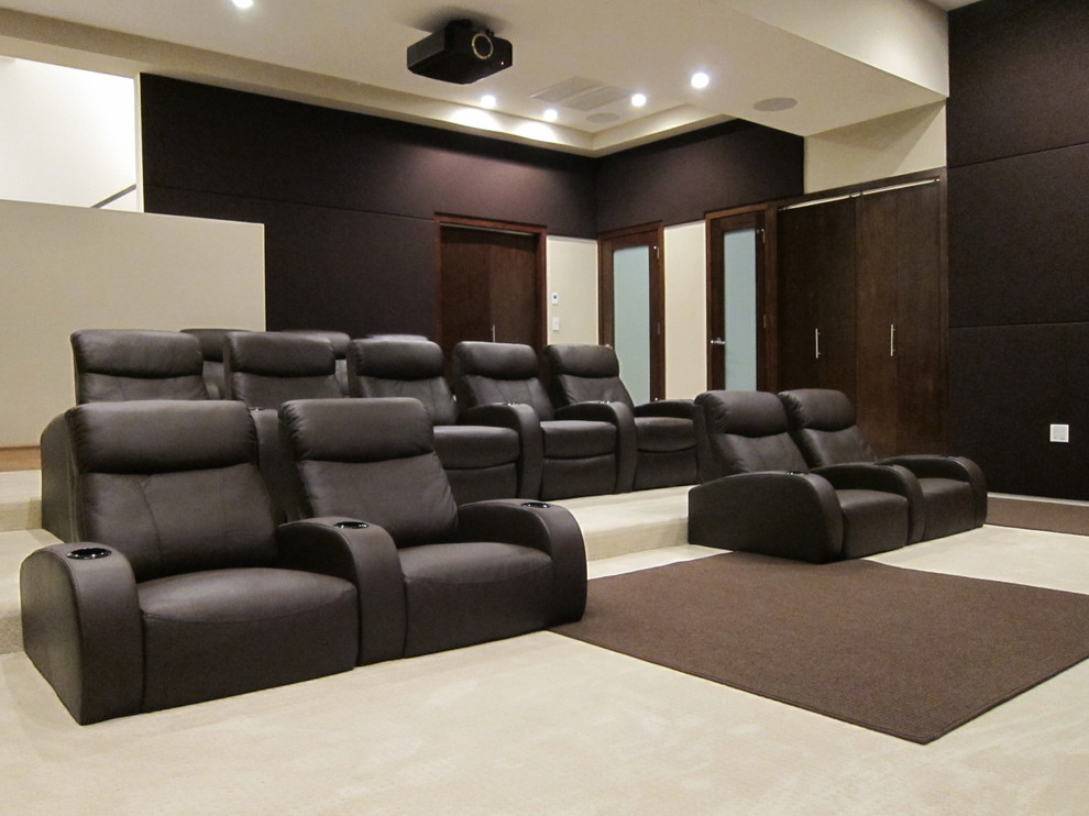Example of a large minimalist enclosed carpeted home theater design in Los Angeles with brown walls and a projector screen