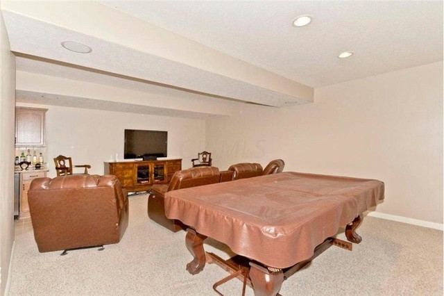 Large elegant enclosed carpeted home theater photo in Columbus with beige walls