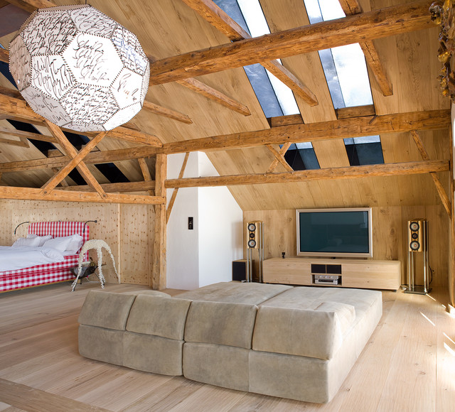 Home theater - mid-sized rustic open concept light wood floor home theater idea in Other with a wall-mounted tv and brown walls