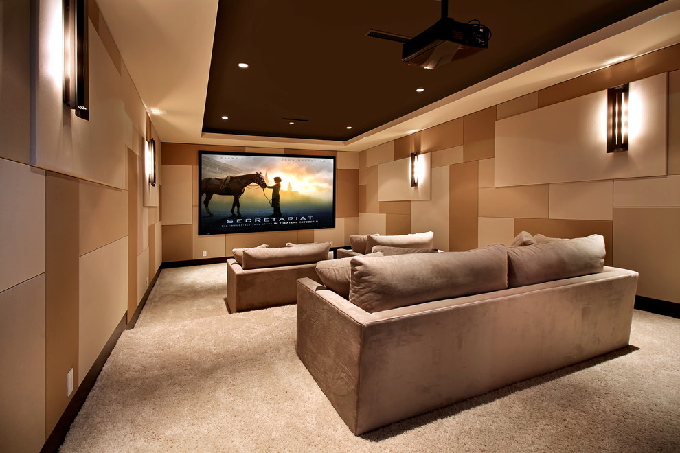 Inspiration for a large contemporary enclosed carpeted and beige floor home theater remodel in Orange County with a projector screen
