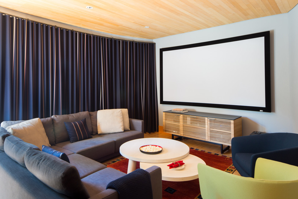 Example of a mid-sized minimalist enclosed light wood floor and brown floor home theater design in Vancouver with gray walls and a projector screen
