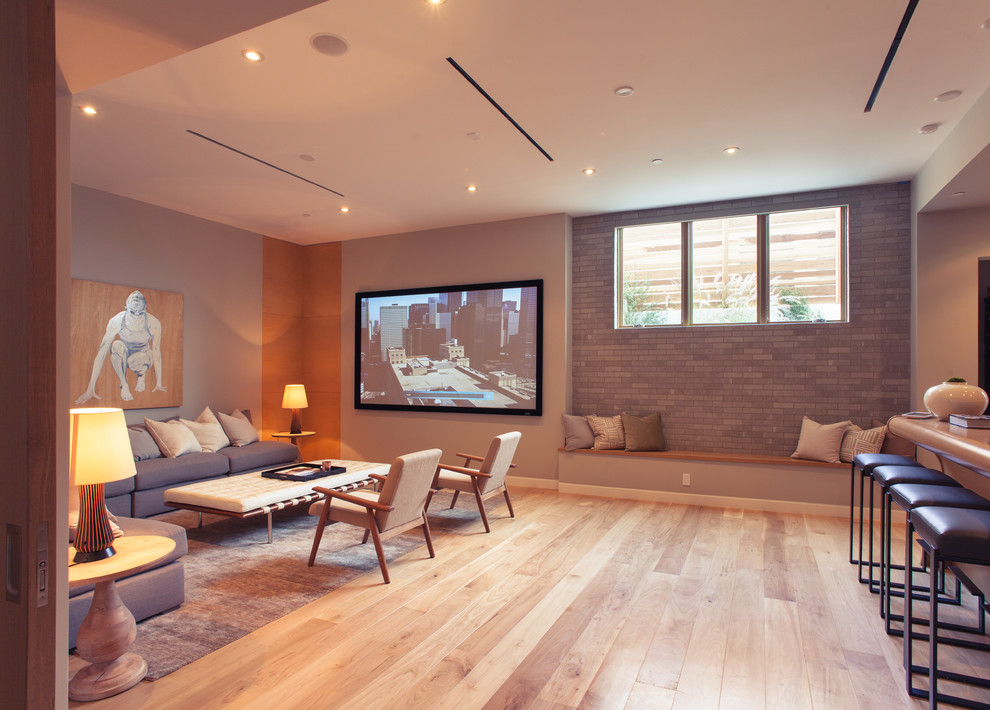 Inspiration for a large contemporary open concept medium tone wood floor home theater remodel in Los Angeles with gray walls and a wall-mounted tv