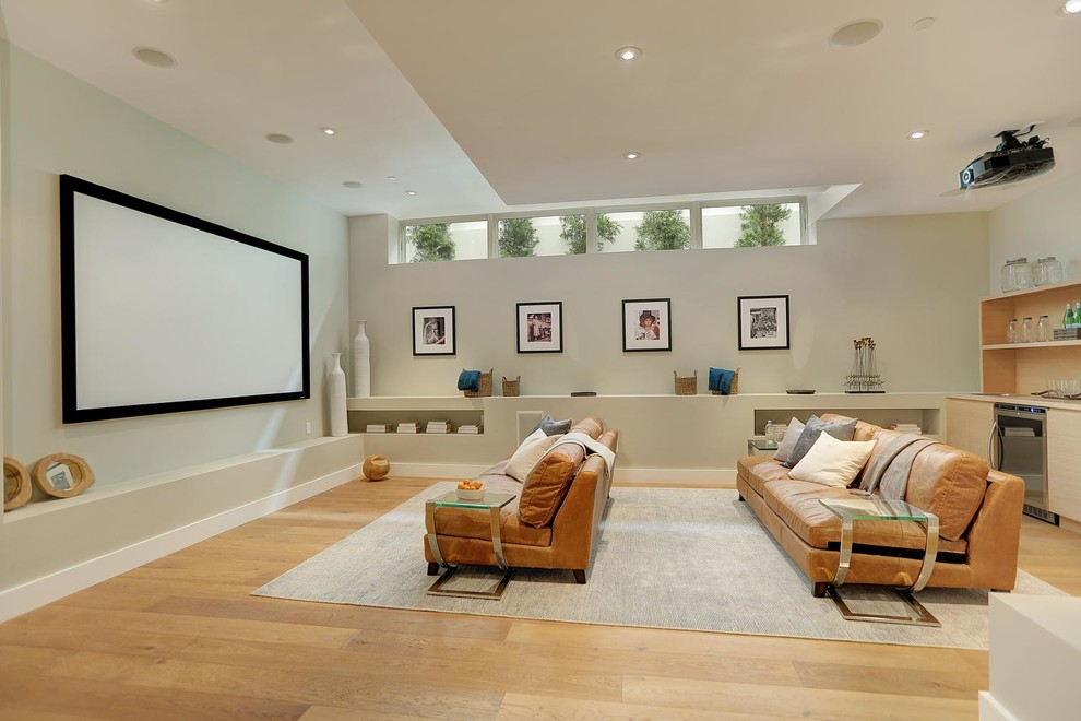 Large minimalist open concept medium tone wood floor home theater photo in Los Angeles with gray walls and a projector screen