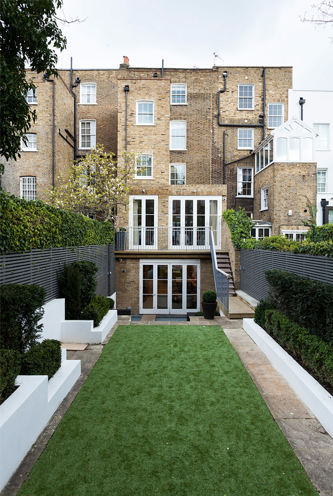 This is an example of a brown contemporary brick exterior in London with a flat roof.