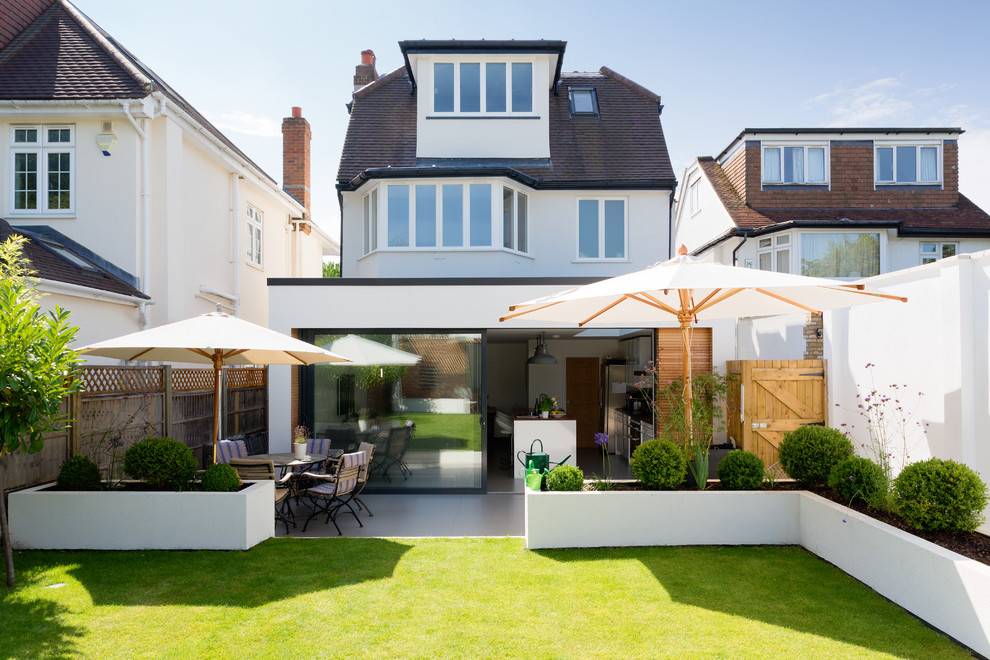 Example of a trendy white three-story exterior home design in London with a clipped gable roof