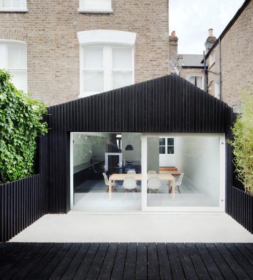 Extension de maison en bardage noir avec terrasse blanche