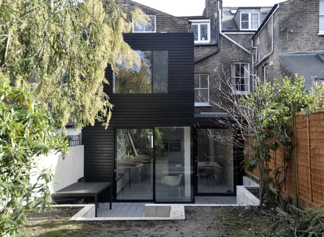 Inspiration for a small and black contemporary exterior in London with wood cladding and a flat roof.