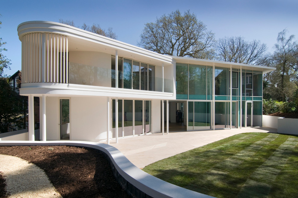 Minimalist white two-story glass exterior home photo in London