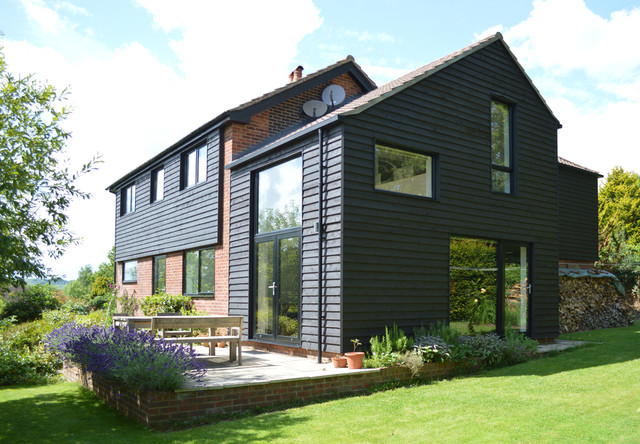 Medium sized and black contemporary two floor exterior in Surrey with wood cladding.