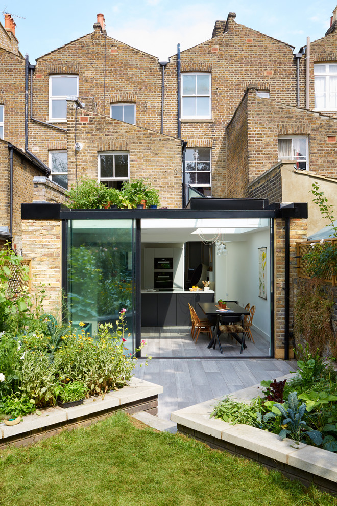 Trendy one-story glass exterior home photo in London