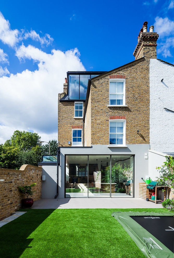 Traditional brown three-story brick gable roof idea in London