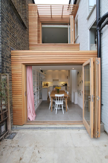 This is an example of a contemporary two floor exterior in London with wood cladding.