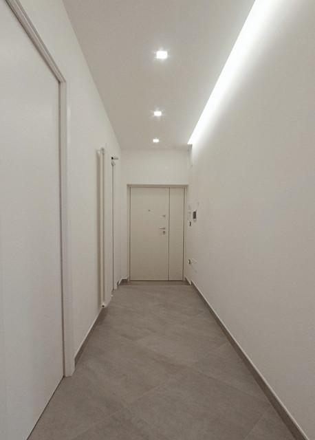Esempio di un ingresso o corridoio design di medie dimensioni con pareti bianche, pavimento in gres porcellanato e pavimento grigio