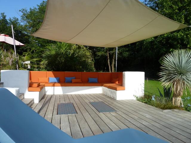 Espace lounge banquette xxl aux coussins g n reux et voile d 39 ombrage sur mesur contemporain for Banquette terrasse