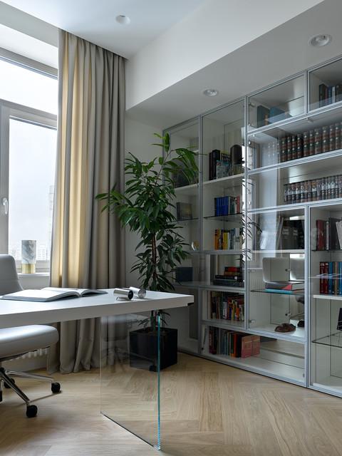Immagine di uno studio design con pareti grigie, parquet chiaro, scrivania incassata, pavimento beige e libreria