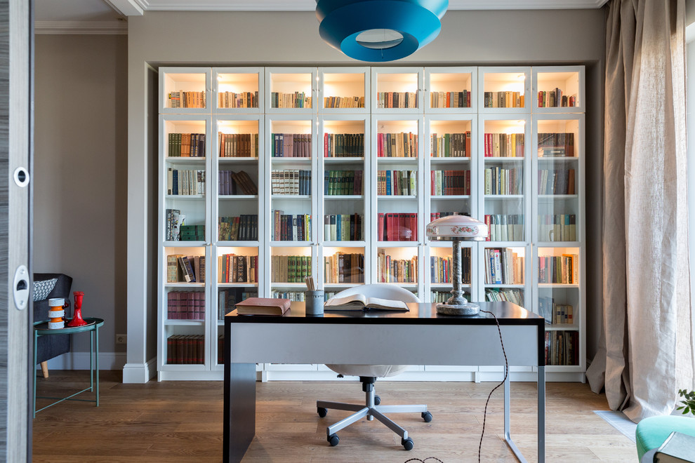 Trendy freestanding desk medium tone wood floor and brown floor home office photo in Moscow with gray walls