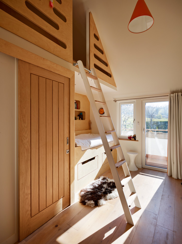 Childrens' room - small contemporary gender-neutral light wood floor childrens' room idea in Devon with white walls