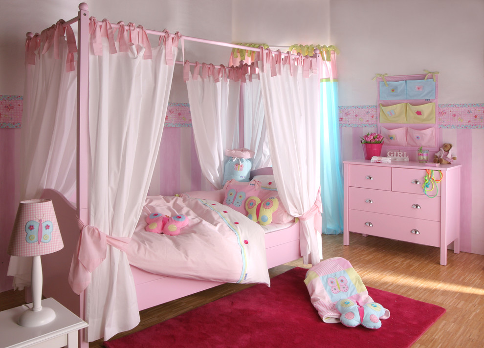 Elegant girl bamboo floor kids' room photo in London with multicolored walls