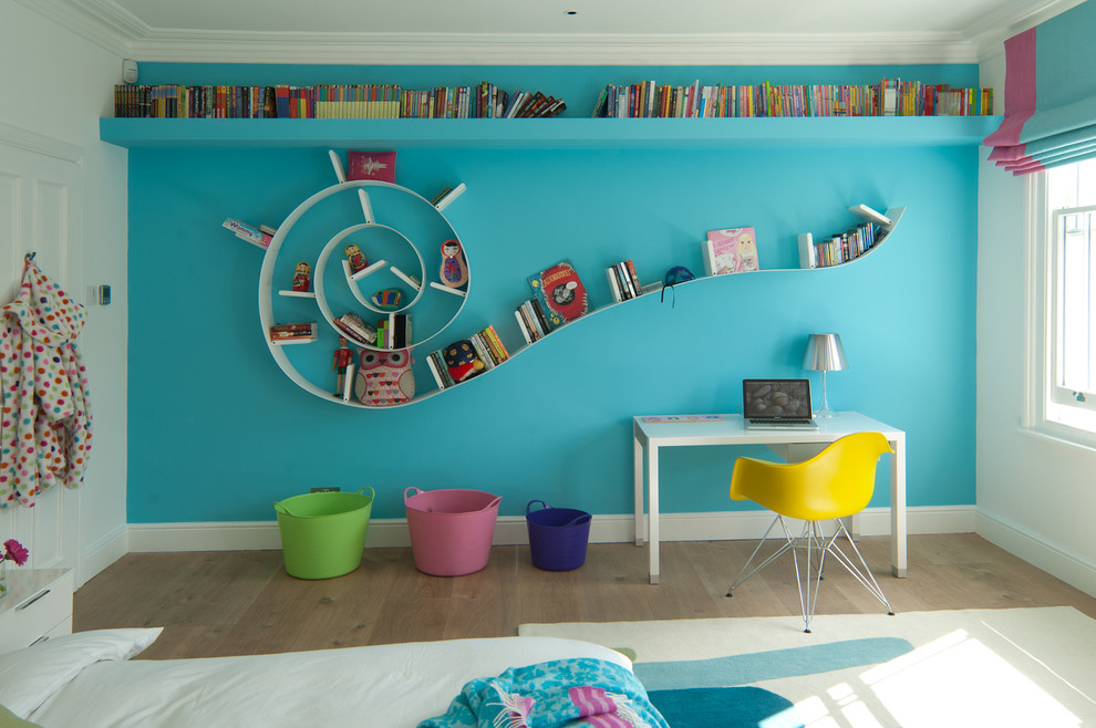 Example of a trendy gender-neutral medium tone wood floor kids' study room design in Kent with multicolored walls