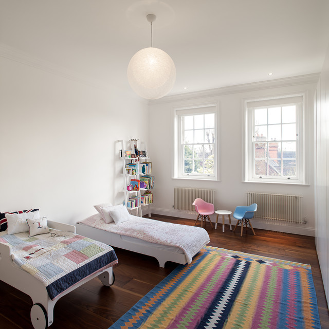 Inspiration for a mid-sized contemporary gender-neutral dark wood floor and brown floor kids' room remodel in London with white walls